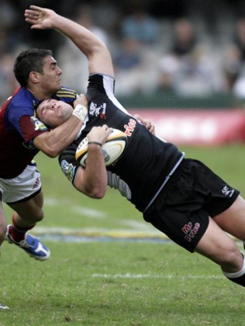 Daniel Bowden, of the Highlanders, tackles Riaan Swanepoel, of the Sharks, during their teams'...