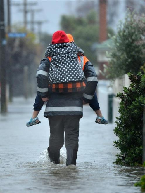 Darren Wilden carries daughter Erica (10) through a flooded South Dunedin street on June 3 last...