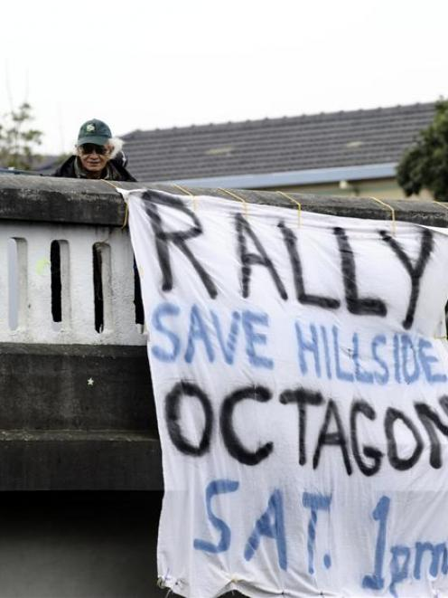 Dave Kearns and Mike Tahana hang a Hillside protest banner from the Roslyn overbridge yesterday....