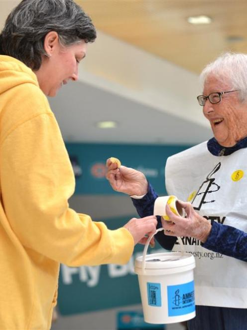Dawn Ibbotson (right) hands out a sticker to Tenoch King while collecting for Amnesty...