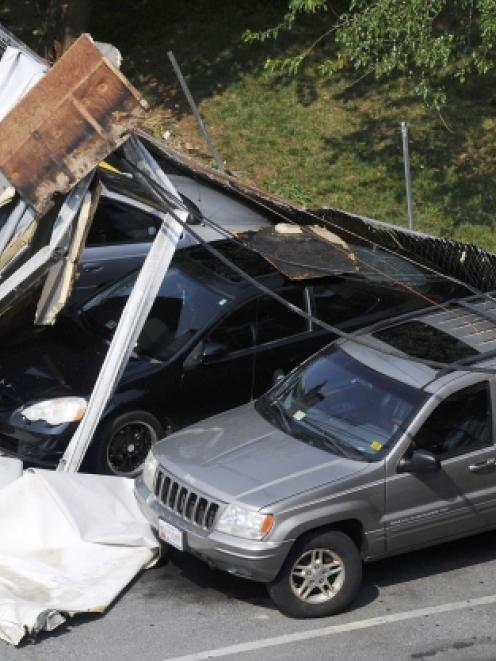 Debris from the storm-damaged Park Tanglewood apartments  sits on cars and utility lines in the...