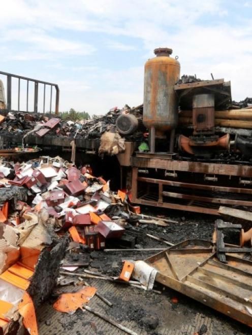 Debris is seen next to a burnt truck after the accident. REUTERS/China Daily