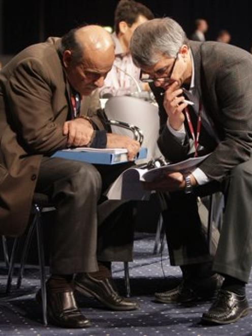 Delegates talk to each other prior to a plenary session at the UN Climate summit in Copenhagen. ...