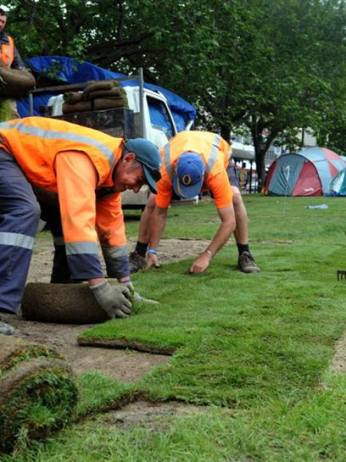 Delta workers Kevin Tansley (on truck), Alan Becker (front left) and Danny Greig work to lay new...