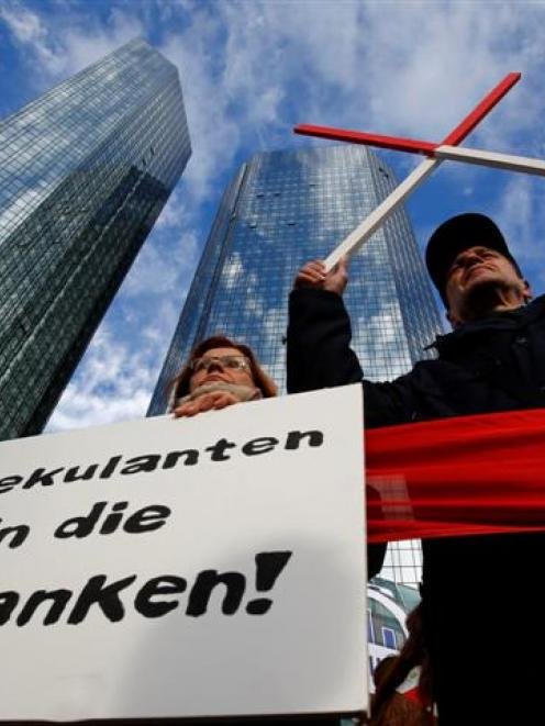 Demonstrators hold a placard in front of the headquarters of Germany's largest business bank,...