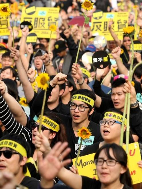 Demonstrators holding sunflowers shout slogans in front of the Presidential Office in Taipei....