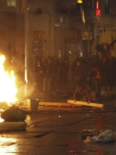 Demonstrators set barricades on fire as they clash with riot police during a protest against...