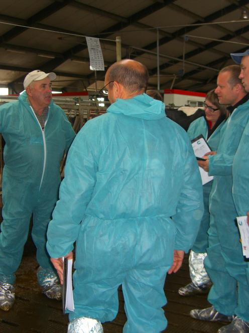 Denis Aitken (wearing the white cap), of Maungatua,  discusses Holstein Friesian characteristics...