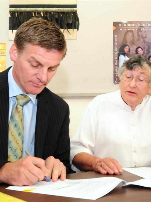 Deputy Prime Minister Bill English and Dame Pat Harrison sign a contract at the Wellness Centre...