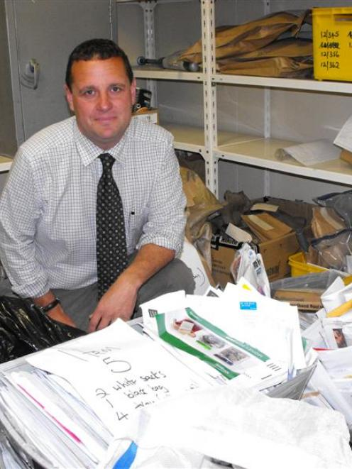 Detective Grant Miller, of Queenstown,  surrounded by  thousands of envelopes and packages...