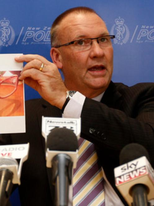 Detective Senior Sergeant Stan Brown holding a picture of glasses believed to be in the...