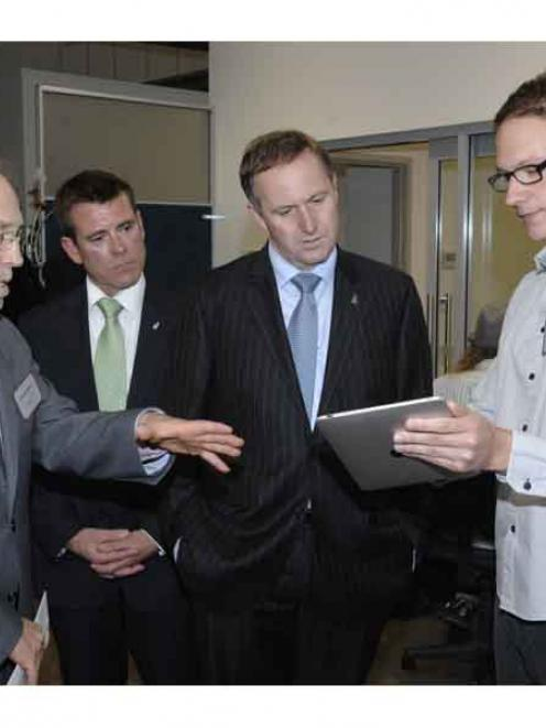 Developer Tim Nixon (right) demonstrates the new Flutter game on Facebook to Prime Minister John...