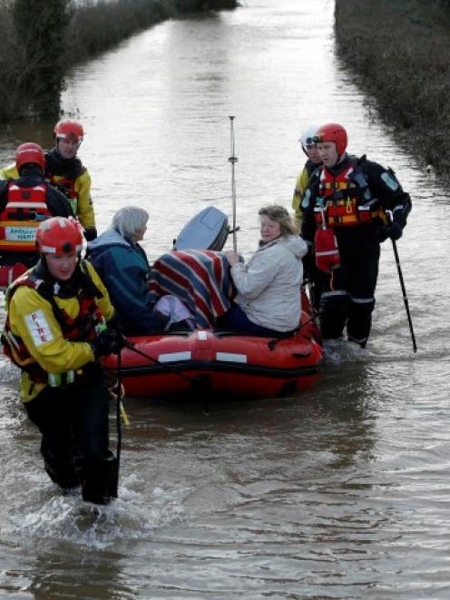 Devon and Somerset Fire and Rescue service members tow stranded residents to safety in...