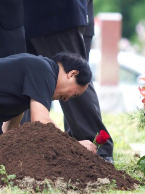 Di Rang Lin, father of slain student Jun Lin lays a rose at his son's gravesite during funeral...