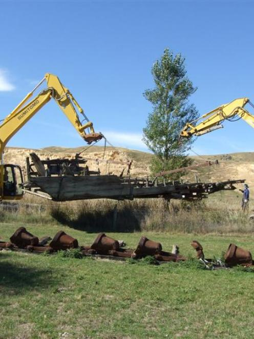 Digger operators Tony Gare (left) and Lindsay McStay manoeuvre the Chatto Creek dredge pontoon on...