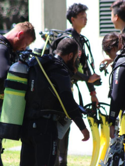 Divers take part in a safety briefing at Mathesons Bay, Leigh, hours after one person in a diving...