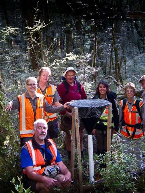 Doc staff and volunteer members of the Matukituki Charitable Trust with one of the eight funnels...
