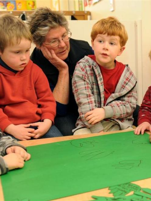 Drawing hand prints as a message of support for the Ako Early Learning Centre are (from left) Nav...