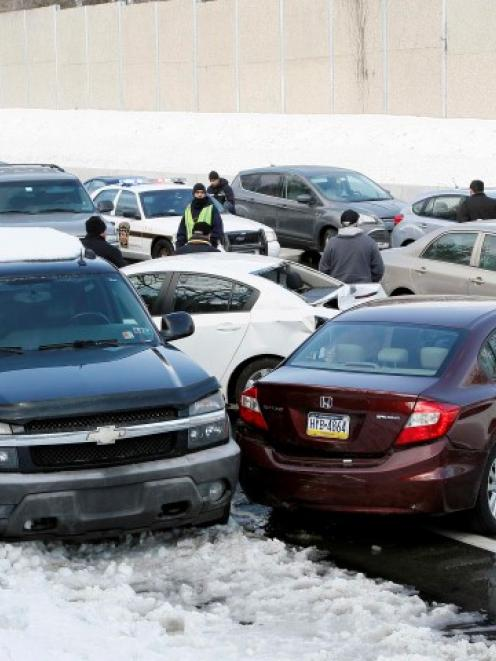 Drivers stand outside their cars as traffic is backed up following a multi-car and truck accident...