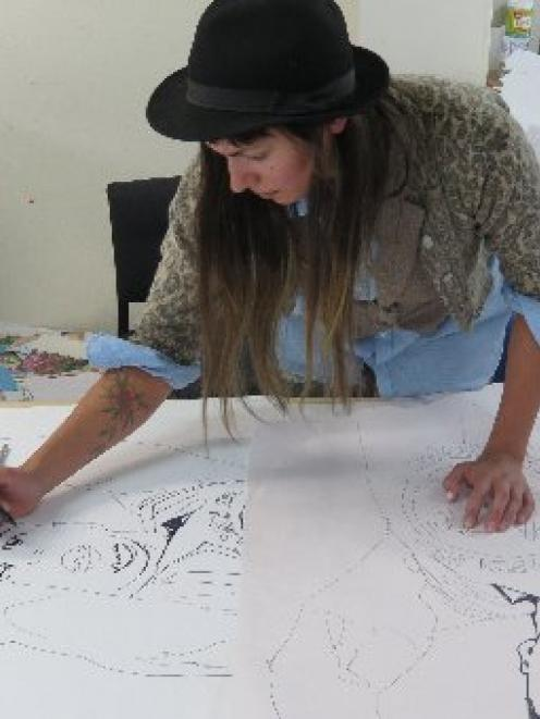 Dunedin artist Aroha Novak works on a stencil for a planned community art wall in Wilkie Rd. ...