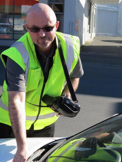Dunedin City Council parking officer Bevan Mears issues an infringement notice. Photo by Jonathan...