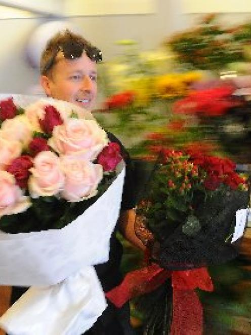Dunedin courier Mike Williamson makes haste as he picks up Valentine's Day flowers for delivery....