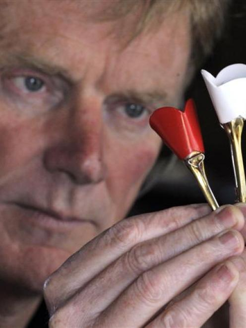 Dunedin jeweller and sculptor Stephen Mulqueen with examples of his poppies fashioned from spent...