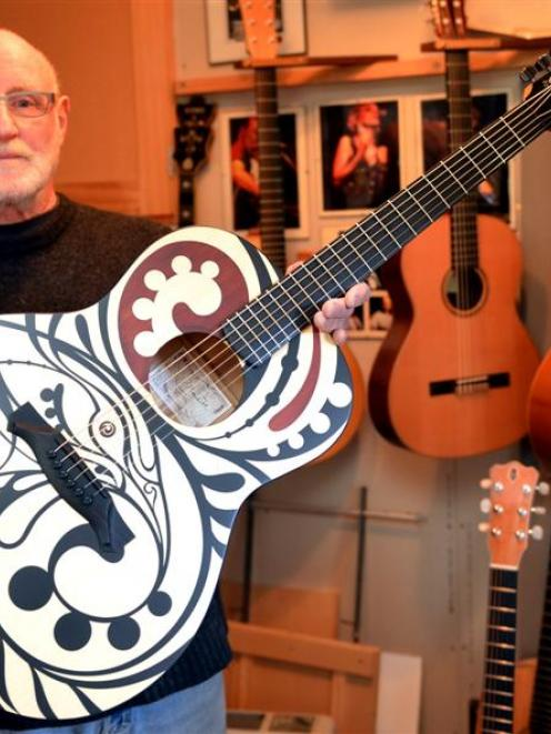 Dunedin luthier Peter Madill with a guitar he made that became a canvas for Auckland artist Shane...