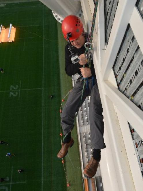 Dunedin Mayor Dave Cull begins his descent for charity from the Forsyth Barr Stadium roof to the...