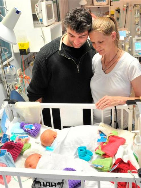 Dunedin parents Alan Bagley and Rebecca Weir look at their 9-day-old twin boys and some knitted...