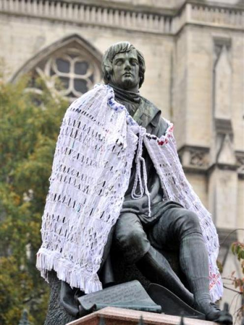 Dunedin's Robbie Burns statue with a cloak designed to draw attention to issues in the fashion...