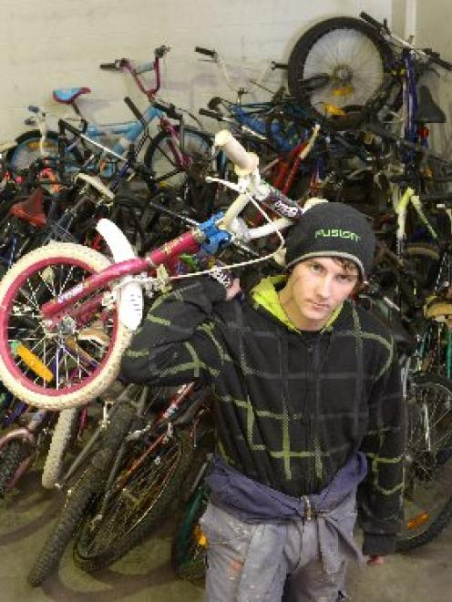 Dunedin Training Centre trainee Zane Grant (17) moves the consignment of Christchurch bikes...