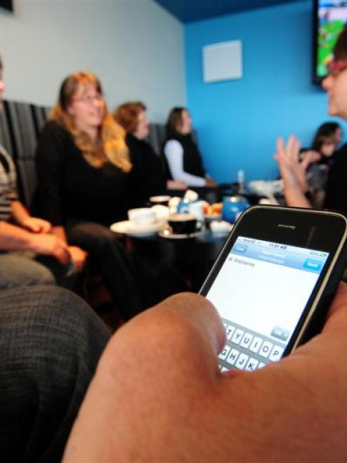 "Dunedin tweeter Paul Le Comte tweets by phone at a ""tweet-up"" at the St Clair Beach Resort..."