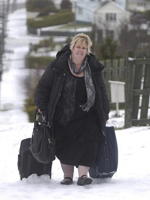 Dunedin woman Delwyn Pauling (41) drags luggage through the snow on Riselaw Rd to her home in...