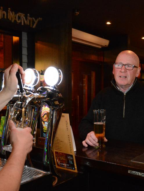 Duty manager Mike Campbell pours a beer as he talks to Ellis Hospitality Group managing director...