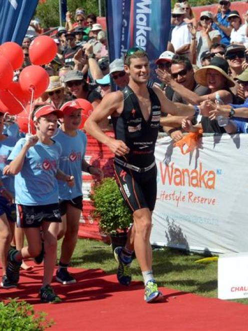 Dylan NcNeice celebrates with the crowd as he runs down the winners shute. Photo by Stephen...