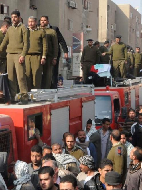 Egyptian police gather around the coffins during the funeral of the five Egyptian policemen who...