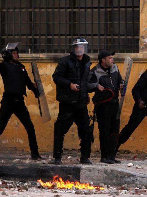 Egyptian police throw stones at protesters during clashes in Alexandria on the second anniversary...