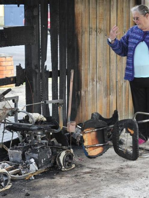 Eleanor Moore inspects the charred remains of her mobility scooter in Mosgiel on Saturday. Photo...