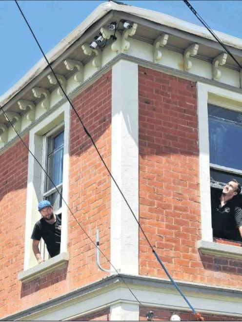 Electricians Craig Sneddon and Devon English install a camera system at 627 Castle St in January....
