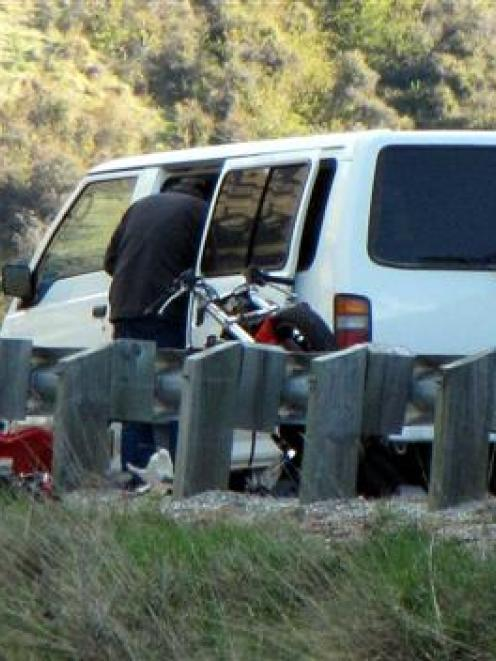 Emergency services attend the crash on the Crown Range Rd on Saturday involving a van and a...