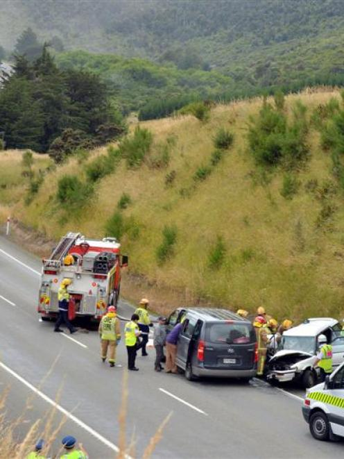 Emergency services work to free the driver of a station wagon involved in a collision with a...