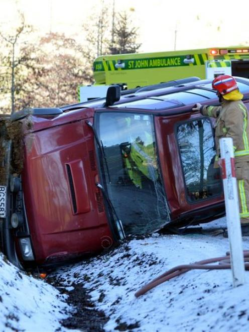 Emergency services work to secure an accident scene after a four-wheel-drive vehicle crashed on...