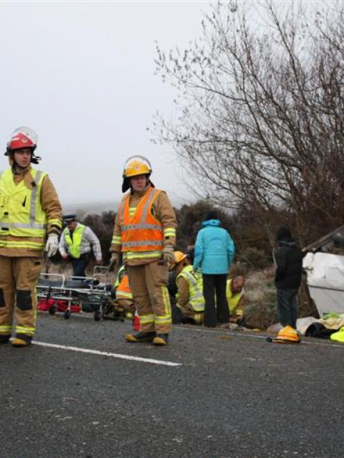 Emergency workers at the scene of a fatal bus crash on the Milford Rd yesterday. Photo by ...