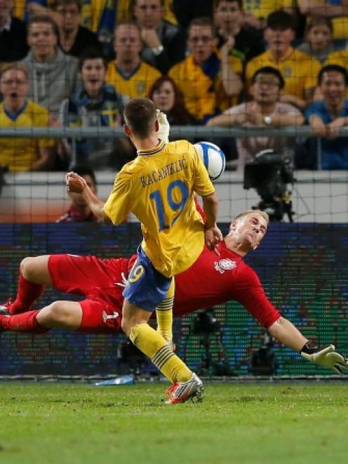 England's goalkeeper Joe Hart saves a shot from Sweden's Alexander Kacaniklic (C) during their...