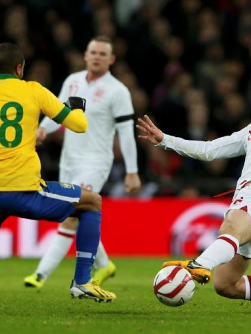 England's Jack Wilshere challenges Brazil's Lucas (L) during their international friendly match...