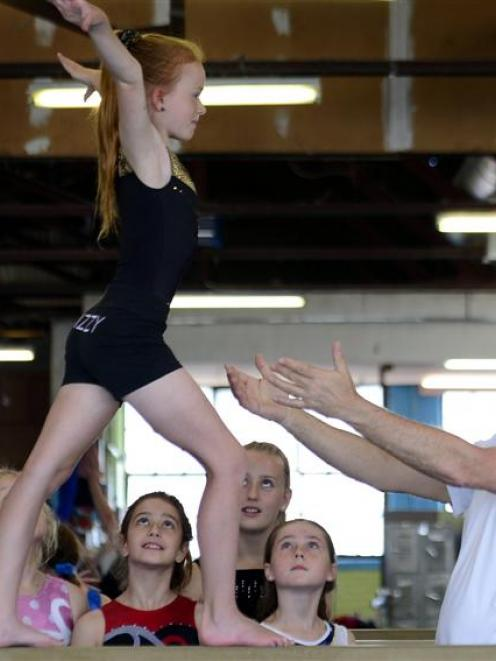 English gymnastics coach Mike Weinstock guides Izzy Johnston (10) as she walks the beam at the...