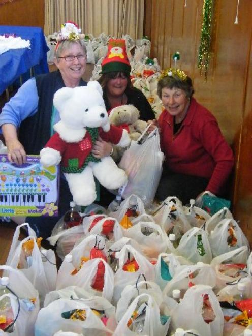 Enjoying preparing food parcels and gifts to distribute to  families in need are (from left)...