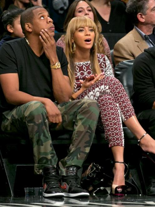 Entertainers Beyonce and Jay-Z (L) watch the Brooklyn Nets play the Toronto Raptors  in the...