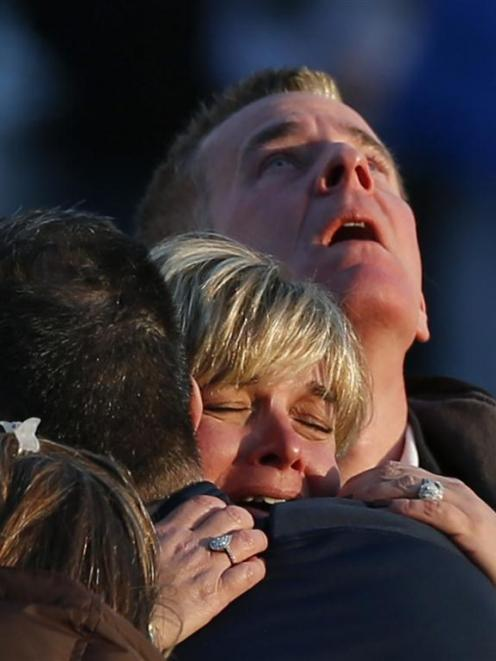 Families grieve outside Sandy Hook Elementary School. Photo by Reuters